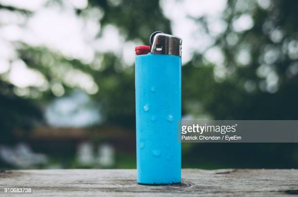 close-up of cigarette lighter on table against trees - cigarette lighter stock pictures, royalty-free photos & images