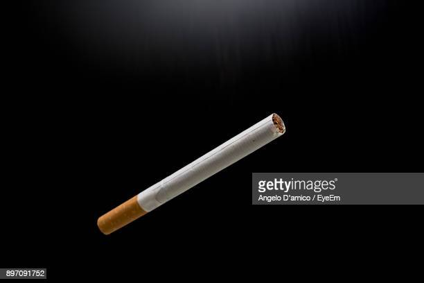 close-up of cigarette over black background - cigarette stock pictures, royalty-free photos & images