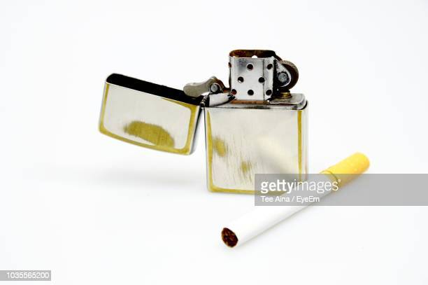 Close-Up Of Cigarette With Lighter Over White Background