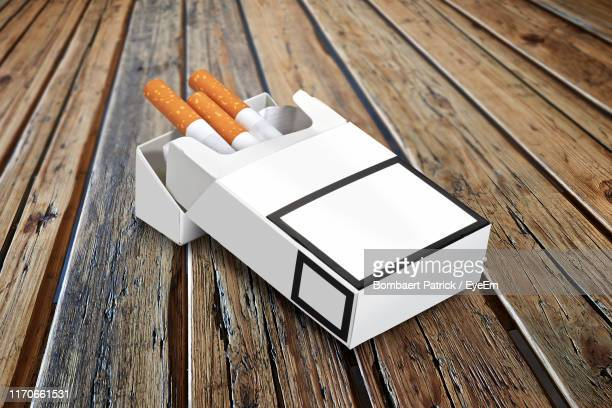 close-up of cigarettes in pack on wooden table - cigarette pack stock pictures, royalty-free photos & images