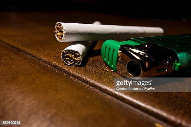 Close-Up Of Cigarettes With Lighter On Table