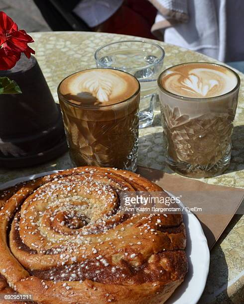Close-Up Of Cinnamon Buns By Coffees Served On Table