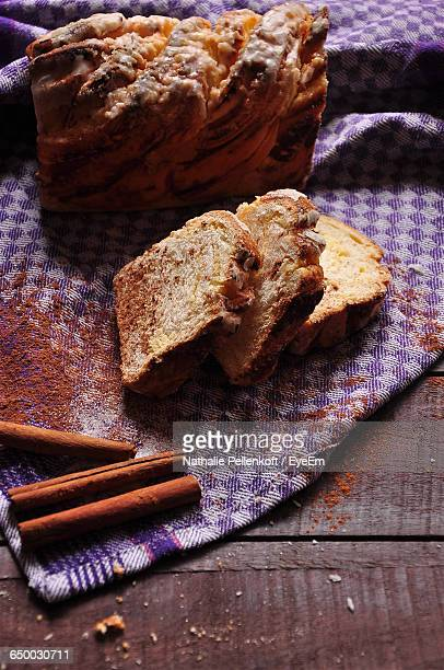 close-up of cinnamon sticks and bread on dishcloth - nathalie pellenkoft stock pictures, royalty-free photos & images