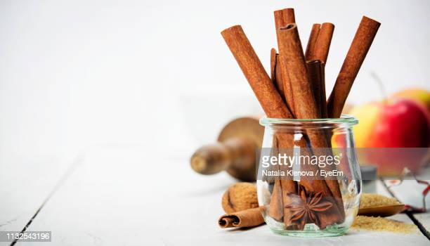 close-up of cinnamon sticks and star anise in glass jar on table - canelo fotografías e imágenes de stock