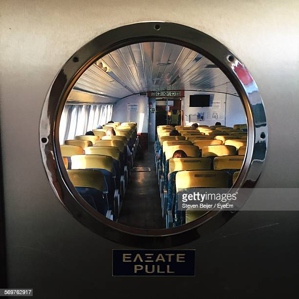 Close-Up Of Circle Window With Seats In Airplane