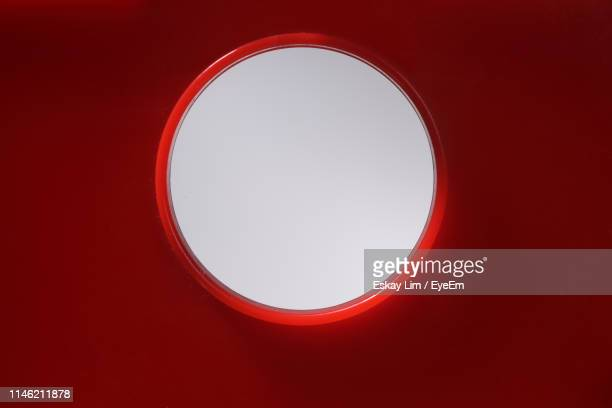 close-up of circled window in red wall - 穴 ストックフォトと画像