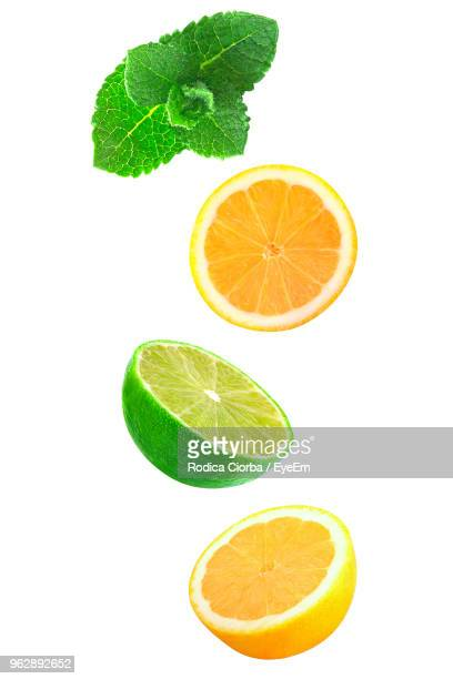 close-up of citrus fruits with mint leaves against white background - lima fotografías e imágenes de stock