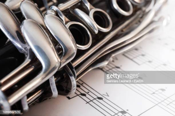 close-up of clarinet on musical notes - clarinetto foto e immagini stock