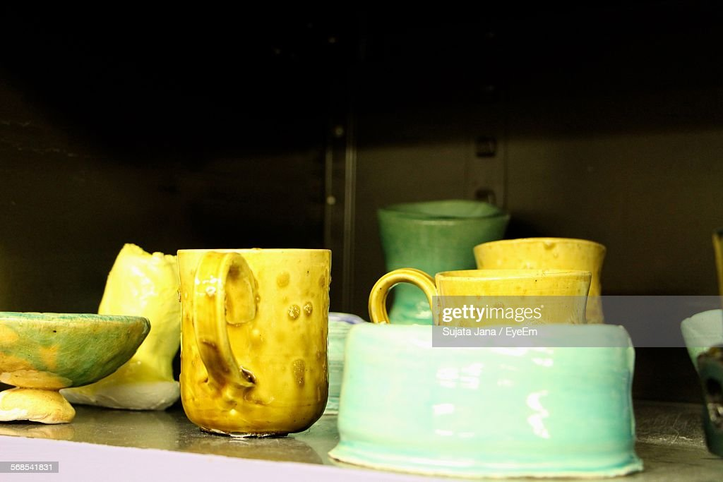 Close-Up Of Clay Cups And Bowls On Shelf : Stock Photo