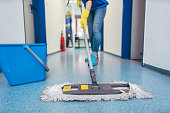 Close-up of cleaners moping the floor