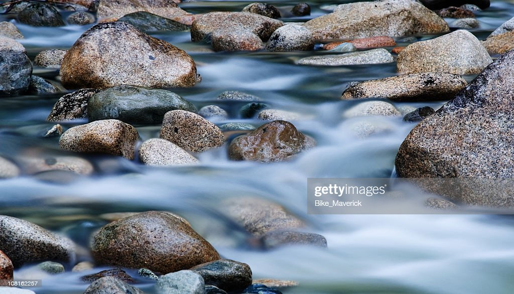 Close-up of clear water flowing through pebbles in stream : Stock Photo
