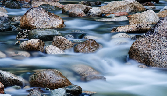 Close-up of clear water flowing through pebbles in stream 108162257