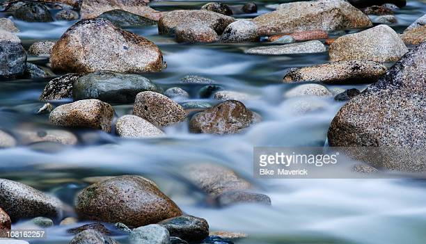 close-up of clear water flowing through pebbles in stream - stream stock pictures, royalty-free photos & images