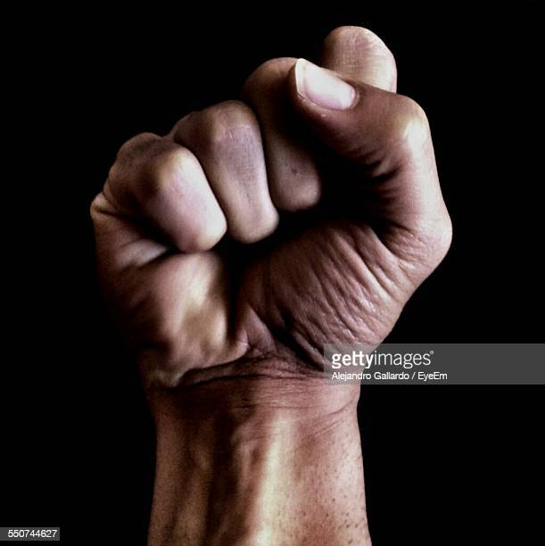 close-up of clenched fist against black background - fist stock pictures, royalty-free photos & images