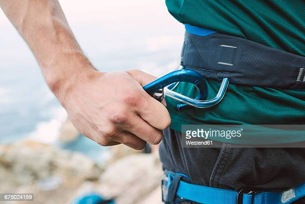 Close-up of climber placing a carabiner in his climbing harness