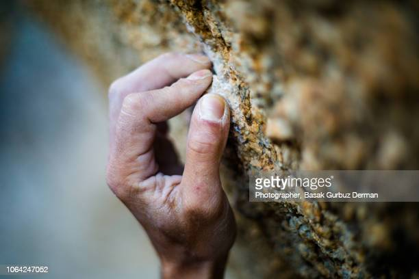 close-up of climber`s hand holding on to rock. - chalk rock stock pictures, royalty-free photos & images