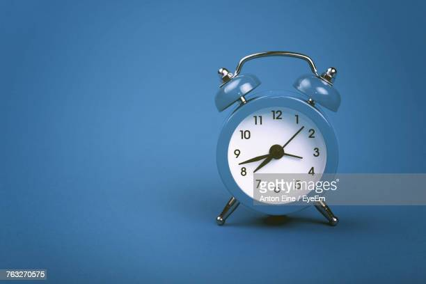 close-up of clock against blue background - man made object stock pictures, royalty-free photos & images