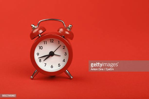 close-up of clock against red background - single object stock pictures, royalty-free photos & images