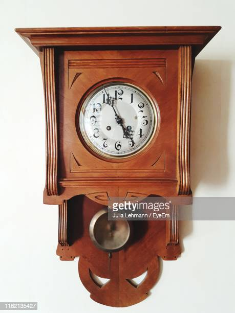 close-up of clock against wall - wall clock stock pictures, royalty-free photos & images