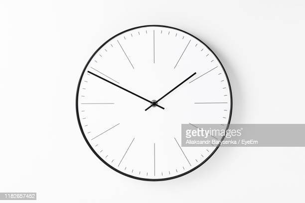 close-up of clock against white background - klok stockfoto's en -beelden