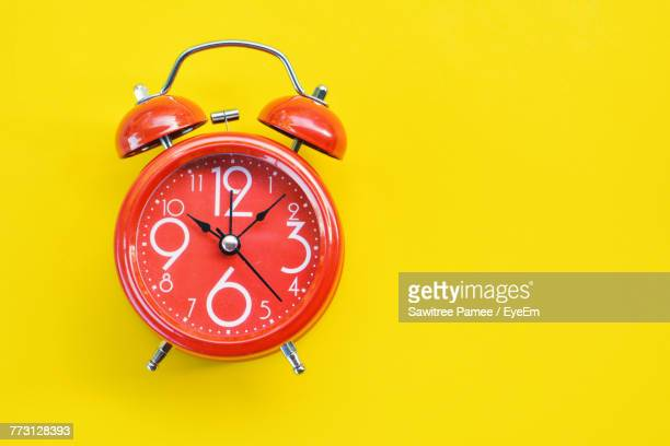 Close-Up Of Clock Against Yellow Background