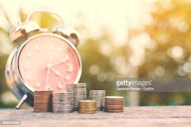 Close-Up Of Clock And Coins On Table