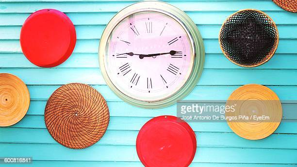 close-up of clock and decorations on wall - wall clock stock photos and pictures