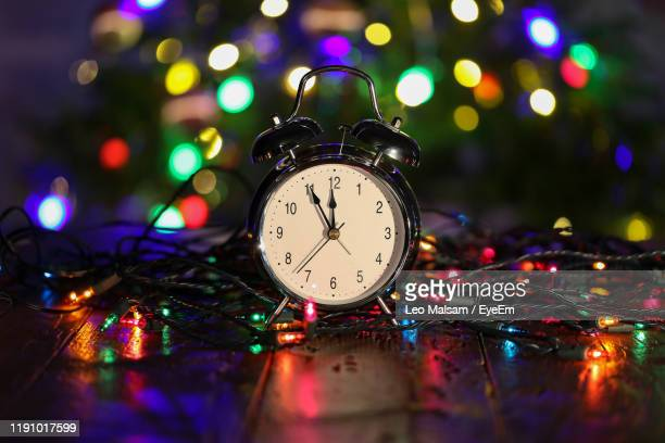 close-up of clock and illuminated christmas lights on table - clock face stock pictures, royalty-free photos & images