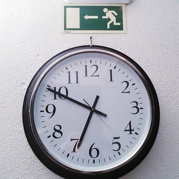Close-Up Of Clock Below Restroom Sign On Wall