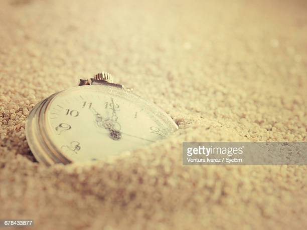 Close-Up Of Clock In Sand