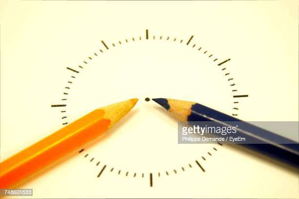 Close-Up Of Clock Made With Colored Pencils On White Paper