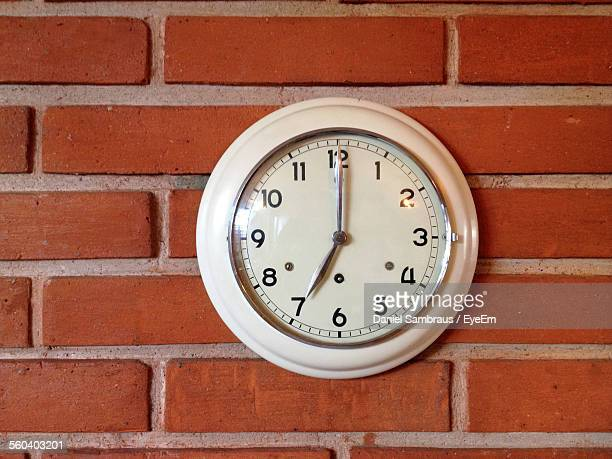 Close-Up Of Clock Mounted On Brick Wall