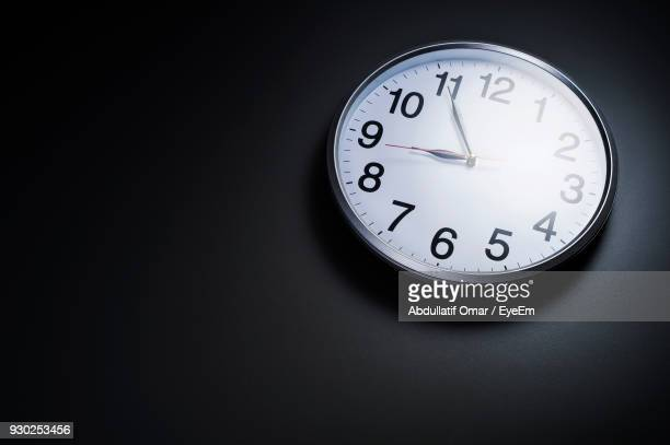 close-up of clock on black background - wall clock stock photos and pictures