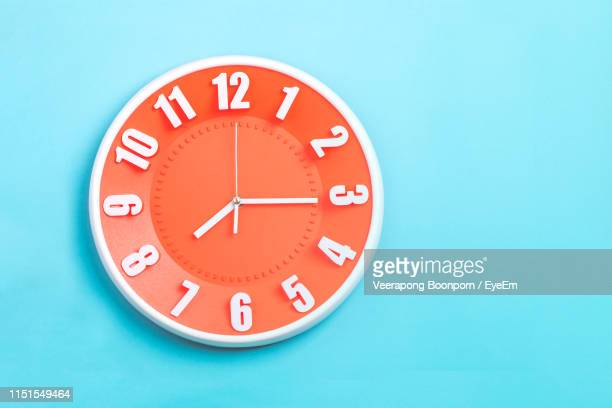 close-up of clock on blue wall - wall clock stock pictures, royalty-free photos & images