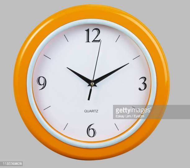 close-up of clock on white background - wall clock stock photos and pictures