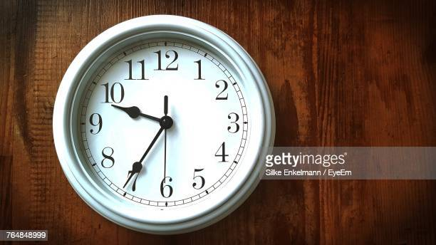 close-up of clock on wooden wall at home - wall clock stock photos and pictures