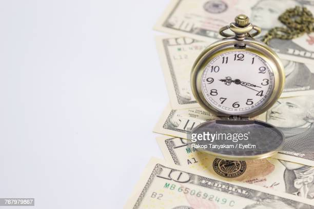 Close-Up Of Clock With Paper Currency Over White Background