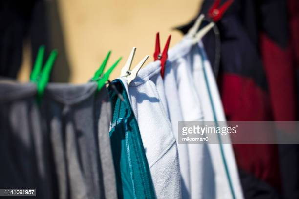 close-up of clothes drying on clothesline. laundry day. - in a row stock pictures, royalty-free photos & images