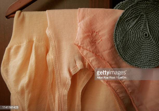 close-up of clothes hanging against wall - aliai foto e immagini stock