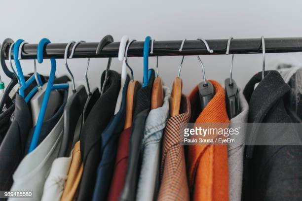 close-up of clothes hanging on coathangers - jas stockfoto's en -beelden