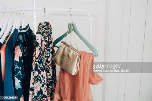 close-up of clothes hanging on rack at home - ontwerp stockfoto's en -beelden