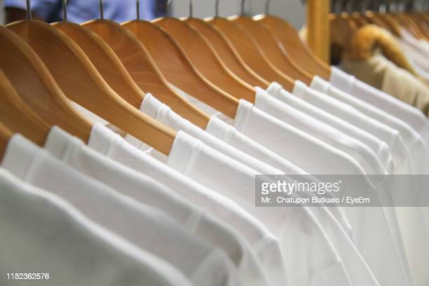 close-up of clothes hanging on rack at store - coathanger stock pictures, royalty-free photos & images