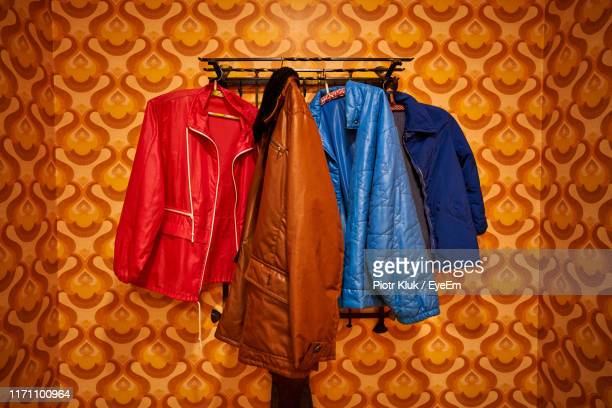 close-up of clothes hanging on wall - jak jas stockfoto's en -beelden