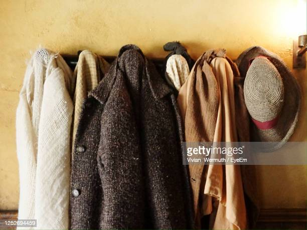close-up of clothes hanging on wooden wall - coat stockfoto's en -beelden