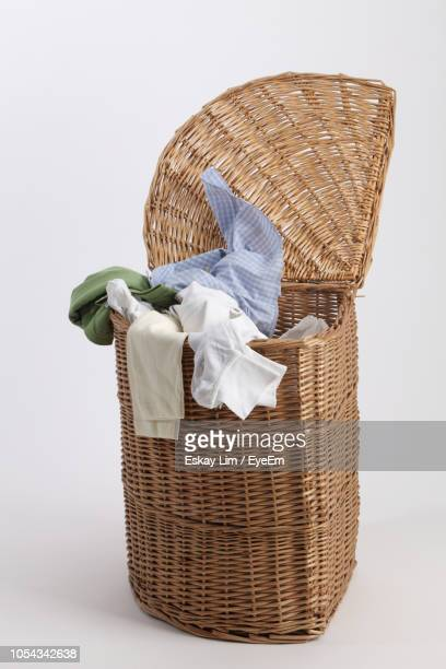 close-up of clothes in laundry basket over white background - 洗濯物 ストックフォトと画像