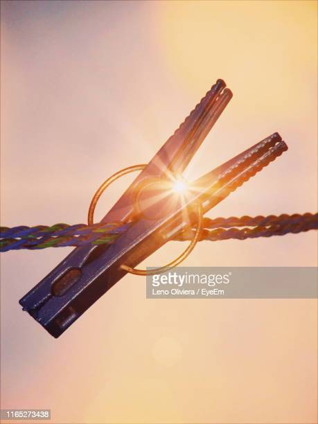 close-up of clothespin on clothesline against orange sky - leno stock pictures, royalty-free photos & images