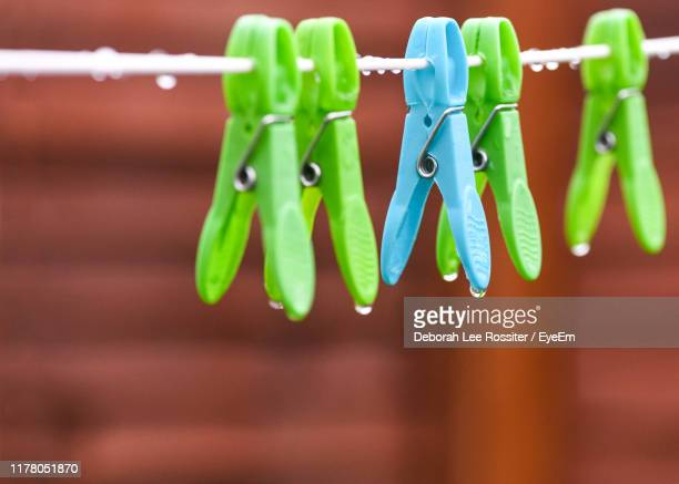 close-up of clothespins hanging on clothesline - clothespin stock pictures, royalty-free photos & images