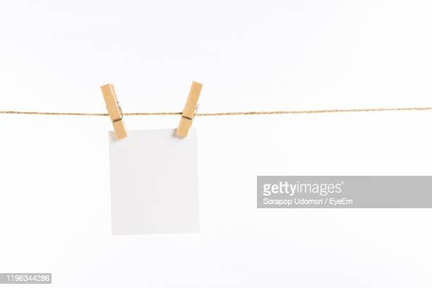 close-up of clothespins with adhesive note hanging on rope against white background - clothespin stock pictures, royalty-free photos & images