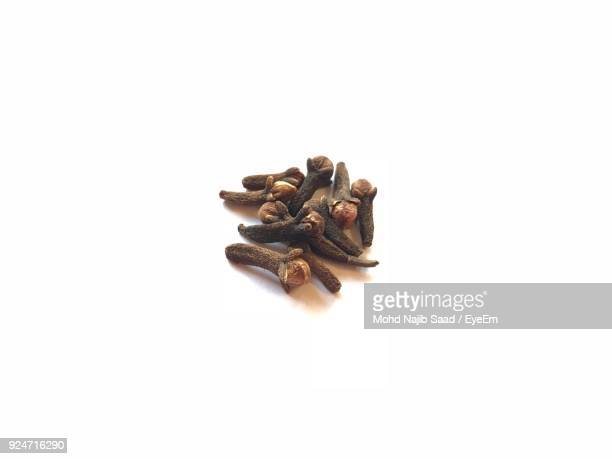 Close-Up Of Cloves Over White Background