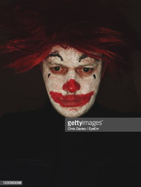 close-up of clown against black background - sad clown stock photos and pictures